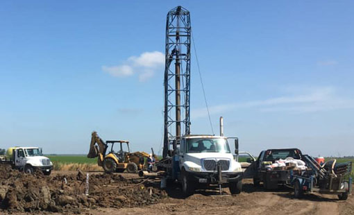 Mid-Valley Drilling Rig drilling a for a well in a field.